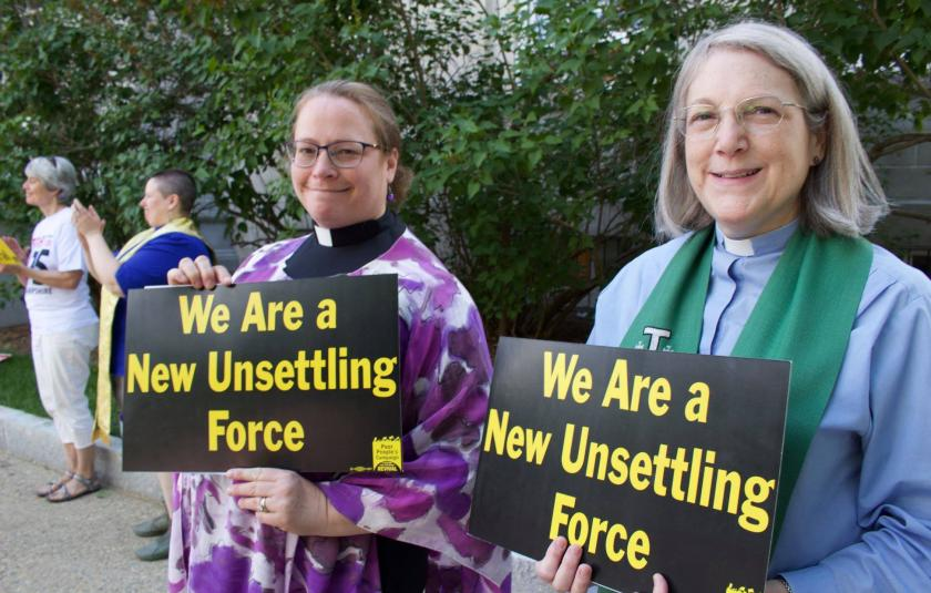 Two women hold signs saying We Are The New Unsettling Force