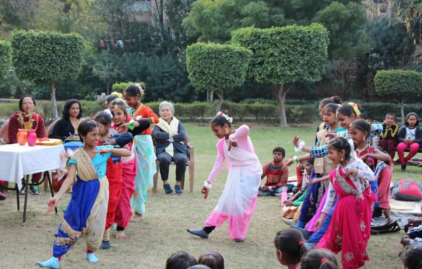 A group of children and adults in a garden surround a girl who is dancing in the middle.
