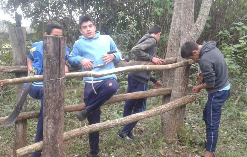 Slideshow: Young boys building a fence.