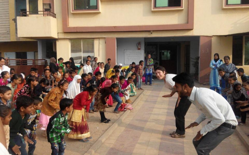 Students at a school in Ahmedabad, India participate in a group warm-up during a URI Environmental Workshop.