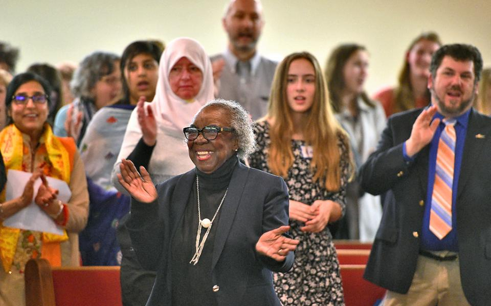 Image Description: Dr. Joan Hillsman leads the audience in the opening song. The 9th Annual World Interfaith Assembly at Southern Missionary Baptist Church, 3143 Midland Ave., Syracuse, photo courtesy of Michael Greenlar | mgreenlar@syracuse.com