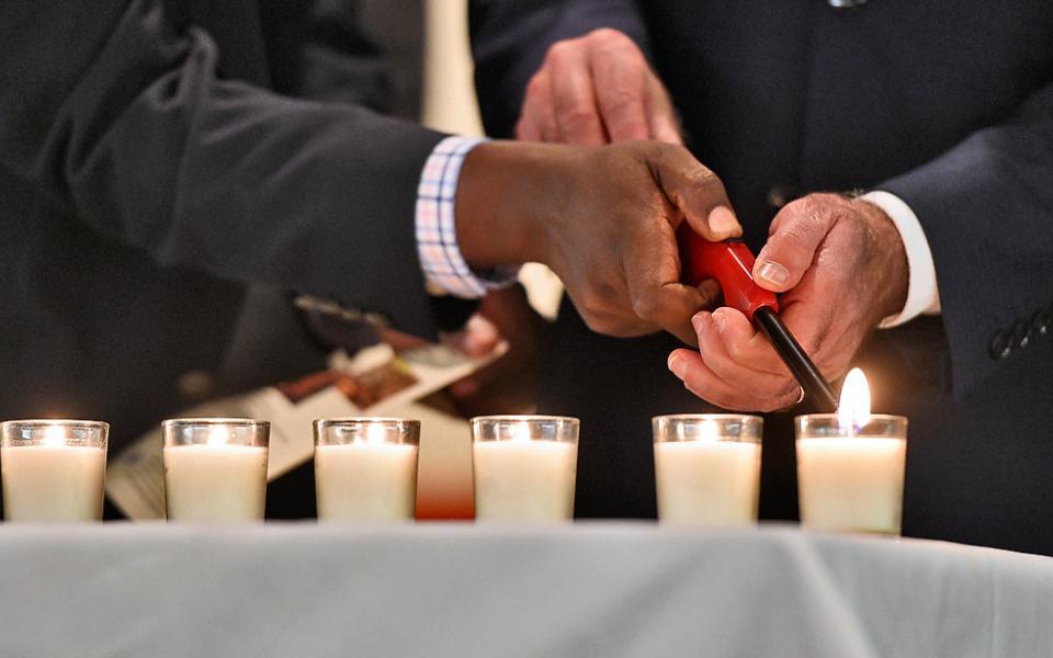 Image Description: Group of different faiths lighting one candle
