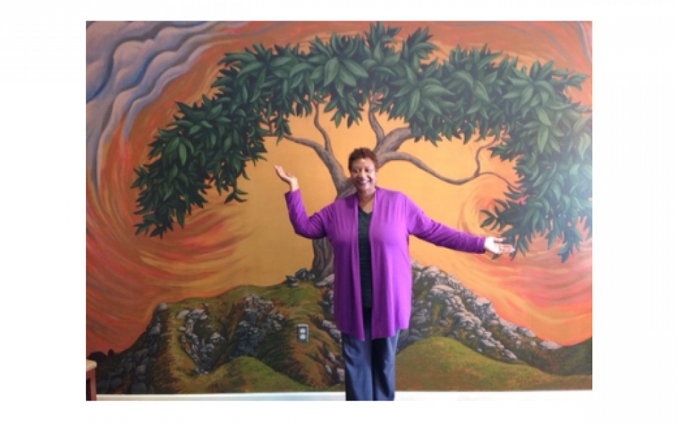 Photo: An image of Reverend Wilkins standing in front of a mural depicting a tree