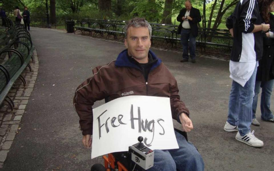 Photo: Gabriel on his wheelchair with a paper written free hugs